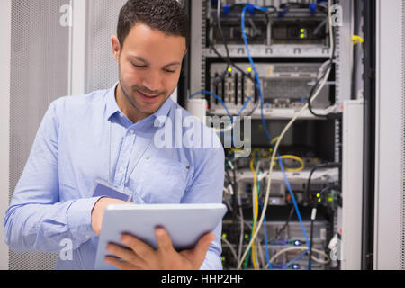 Data centre worker with tablet computer in data centre - Stock Photo