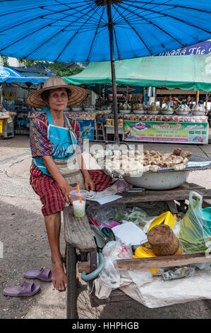 A barefoot woman cooks food on a grill in a table which is powered by a three-wheeled bicycle at the Nong Khai street - Stock Photo