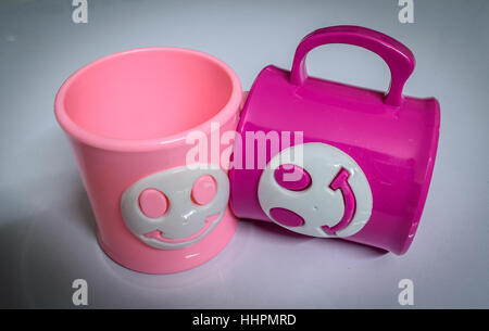 Colourful cups on a glossy white table. - Stock Photo