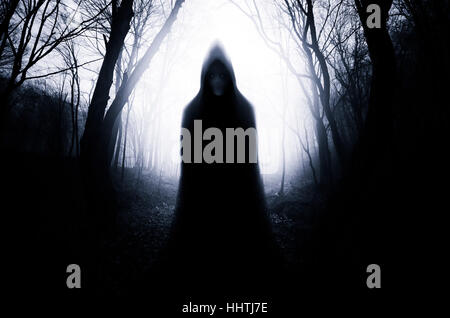 Scary ghostly figure in forest at night, gloomy Halloween scene - Stock Photo