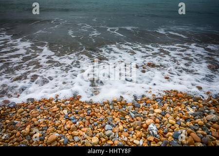 Colorful stones and peebles on a beach on a cold day in autumn - Stock Photo