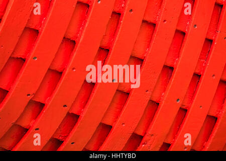 Red rows of painted wooden side of a fishermen boat - Stock Photo