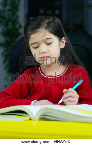 Six year old girl doing her homework at night. - Stock Photo