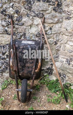 An old rusty metal cartwheel leaning on wall - Stock Photo