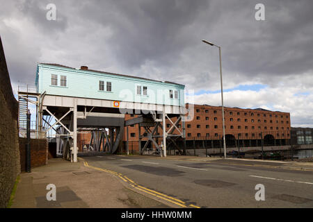 The machine room of the Stanley Docks bascule Bridge with the Tobacco Warehouse in the background - Stock Photo