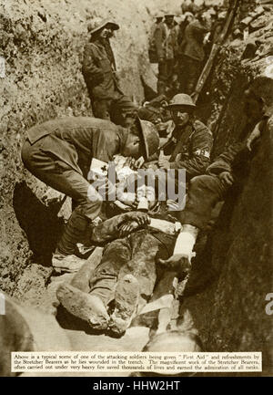 Wounded British soldier being given first aid by a stretcher bearer in the trenches, First World War, 1916 - Stock Photo