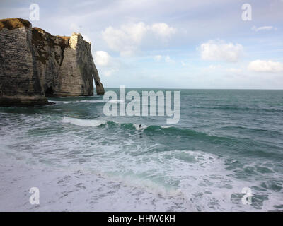 View on Falaise d'Etretat with surfer in the water - Stock Photo