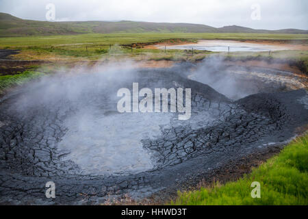 Bubbling mud pools at the Krysuvik Geothermal Area in Reykjanes Peninsula of Southern Iceland - Stock Photo