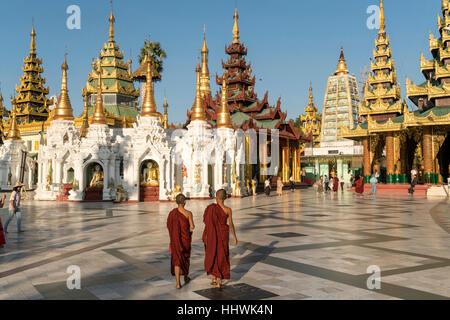 Monks in front of Shwedagon Zedi Daw, Shwedagon Pagoda, Yangon, Myanmar - Stock Photo