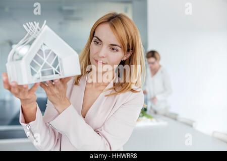 Female architect examining model in office - Stock Photo