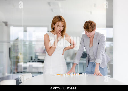 Female architects examining model in conference room - Stock Photo