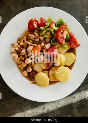 Tasty chicken meat with potatoes, tomatoes, sweet corn and more vegetables. Homemade - Stock Photo