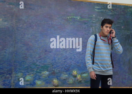 Young visitor uses an audio guide in front of the paintings from the cycle Nympheas (Water Lilies, 1920-1926) by - Stock Photo