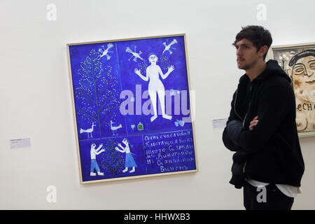 Visitor in front of the painting Autumn (1912) by Russian avant-garde painter Mikhail Larionov displayed in the - Stock Photo