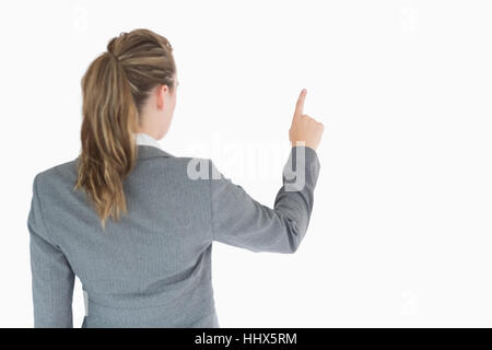 Businesswoman at rear touching on something in the air - Stock Photo