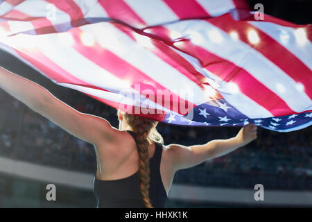 Female athlete running victory lap with American flag - Stock Photo