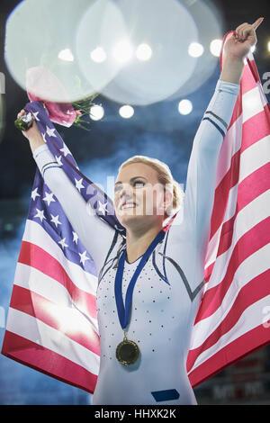 Smiling female gymnast celebrating victory holding American flag - Stock Photo