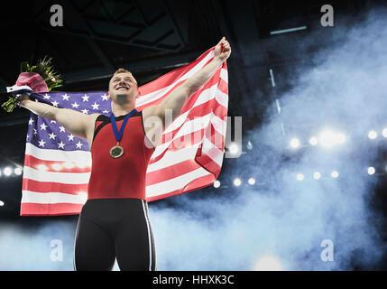 Male gymnast celebrating victory holding American flag on winners podium - Stock Photo