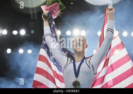 Enthusiastic female gymnast celebrating victory holding American flag on winners podium - Stock Photo