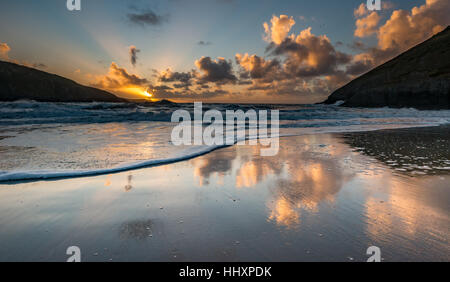 Sunset reflected in shallow water with foam on the beach in Mwnt, Wales, UK. September. - Stock Photo