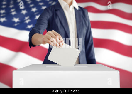 Woman putting a ballot into a voting box with USA flag on background. - Stock Photo