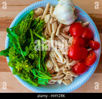 A dish the ingredients for the typical flat Bari: orecchiette with turnip tops. Orecchiette, tomatoes, garlic and - Stock Photo