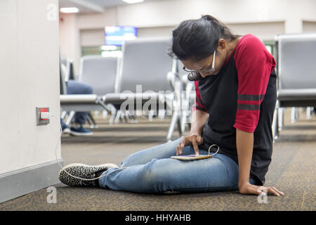 young woman sit on floor and recharges the phone from the wall socket in the hall - Stock Photo