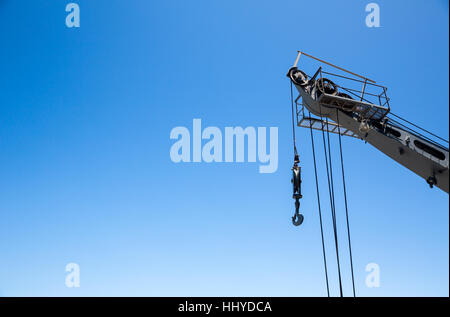Crane with risen boom on blue sky background - Stock Photo