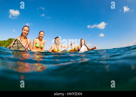 Girls in bikini - group of surfers on surf boards, women wait for ocean wave People in water sport adventure camp, - Stock Photo