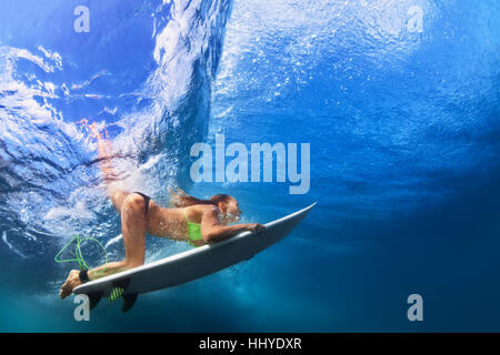 Active girl in bikini in action. Surfer woman with surf board dive underwater under breaking wave. Water sports, - Stock Photo
