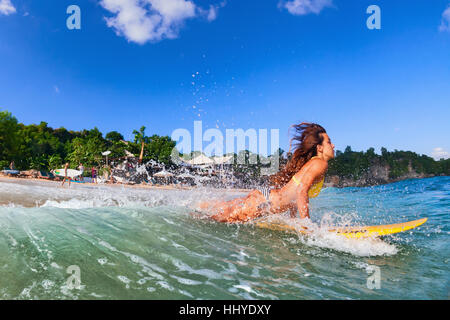 Girl action on surf board - woman surfer run into water, jump through ocean wave. People in water sport camp, beach - Stock Photo
