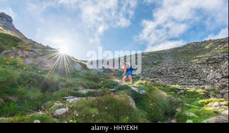 Female hiker on footpath in mountains, sun shines over ridge, ascend Greifenberg, Schladminger Tauern, Styria, Austria - Stock Photo