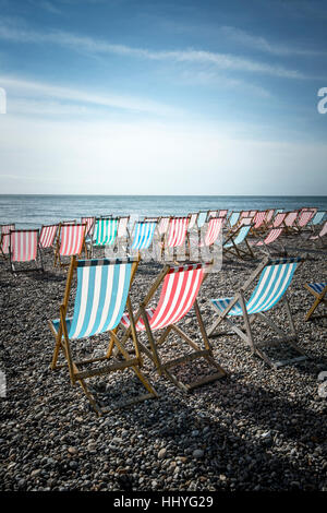Empty deck chairs arranged on a beach - Stock Photo