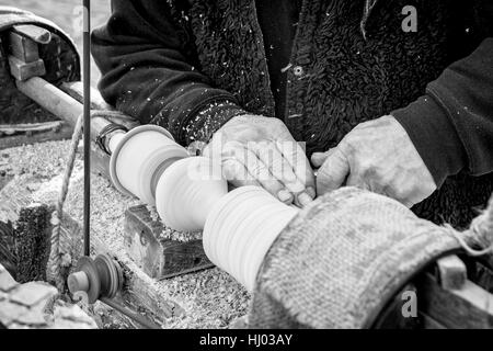 An artisan carves a piece of wood using an old manual lathe. - Stock Photo