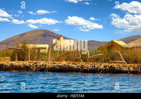 Manmade floating island with a sign spelling out Titikaka on Lake Titicaca in Peru - Stock Photo