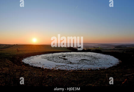 Brighton, UK. 21st Jan, 2017. The sun rises over a dew pond on the South Downs Way at Ditchling Beacon just north - Stock Photo