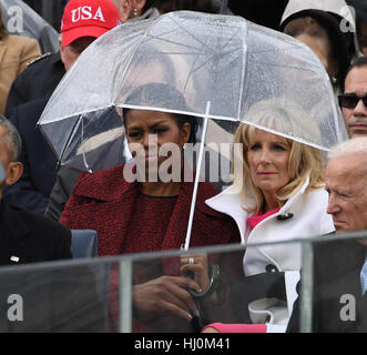 Michelle Obama and Dr. Jill Biden share an umbrella as President Donald Trump delivers his inaugural address at - Stock Photo