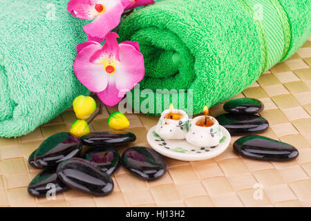 Spa set with towels, candles, stones and flowers on bamboo background. - Stock Photo