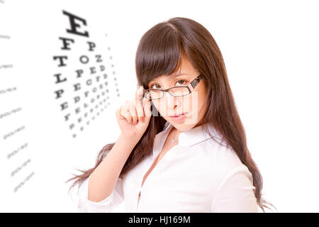 Chinese woman peering over the top of her spectacles, with eyesight test chart - Stock Photo