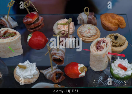 types of canapes for cocktails on a glass plate, note shallow depth of field - Stock Photo