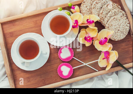 Breakfast in bed in Valentines day. Cup of tea and sweet candies. Love or holiday concept. - Stock Photo