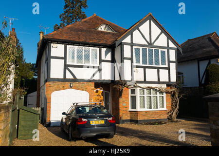Mock Tudor 1930's house with car on the drive, and garage, in Esher, Surrey. UK. - Stock Photo