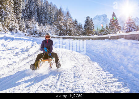 Cheerful girl riding a sled downhill on a snow covered sledge trail in a white sunny winter mountain landscape - Stock Photo