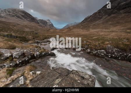 Area of Glencoe, Scotland. Picturesque dramatic view of Glencoe with the River Coe in the foreground. - Stock Photo