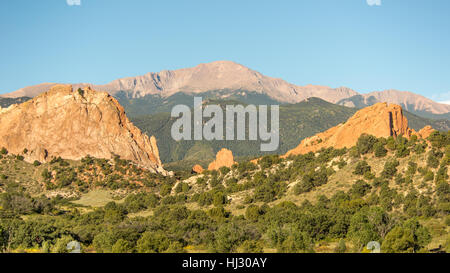 Morning light illuminates Pikes Peak, towering over South Gateway, North Gateway, Kissing Camels, and the Tower - Stock Photo