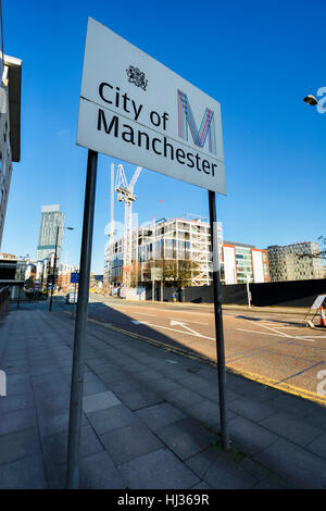 City of Manchester sign on Medlock Street, Manchester City centre with construction site in background. - Stock Photo