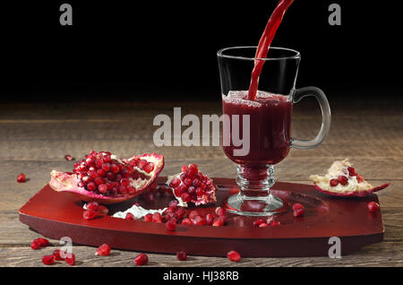 Pomegranate juice is poured into a glass Cup, wooden surface and black background. Selective focus. - Stock Photo