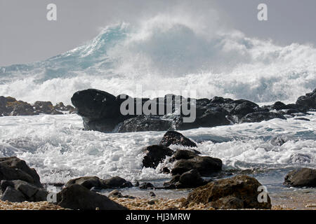 Powerful waves break on the rocks at Kaena Point, North Shore, Oahu, Hawaii, USA - Stock Photo
