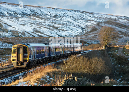 Settle, UK - 10 November 2016. Northern service train passes through Little Dale valley approaching Ribblehead viaduct. - Stock Photo