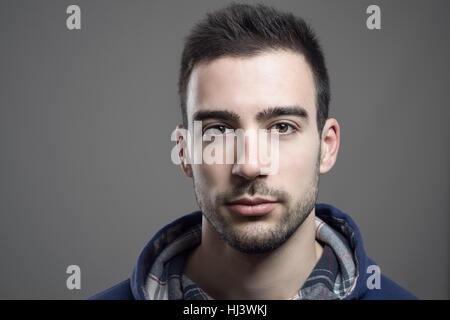 Close up of serious young unshaven man wearing hoodie looking at camera - Stock Photo